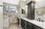 Master bathroom with dual vanity sinks and custom tile work throughout.