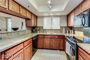 Kitchen with eat-in bar, matching black appliances, granite counter tops and double stainless sink.