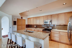 Kitchen features an abundance of upgraded cabinets, stainless appliances, granite countertops, pull out shelving, glass backsplash and eat at island.