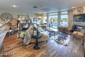 Spacious living room with large windows and sliders to the back patio to enjoy those beautiful sunsets!
