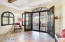 Dramatic iron doors lead to covered patio