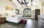 Dramatic bedroom with beams and vaulted ceiling