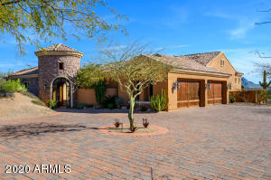 ** Multiple Offers Received! ** This stunning custom home in gated Troon Verde features a 3BR/2.5BA main house & 1BR/1BA detached casita, all connected by an enclosed outdoor courtyard with water feature & gas fireplace. Nestled on a 1.687 acre corner lot with protected, sweeping views of the McDowells & Pinnacle Peak, this home seamlessly blends indoor & outdoor living at every turn. Main home features a split floorplan centered around a lg. great room with an arched, brick ceiling, custom stonework, & retractable wall of glass. Chef's kitchen is appointed with Viking appliances, Subzero refrigerator/freezer, copper farm sink & oversized island. Stone floors & custom Alder cabinetry throughout. Backyard oasis boasts a covered patio, negative edge pool, spa, swim up bar & built-in BBQ.