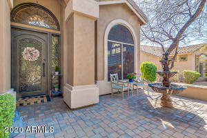 Enter to a pavered courtyard & beautiful custom iron entry door