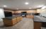 The u-shaped kitchen and kitchen island offer plenty of cabinet space in the maple cabinets. The countertops are made of grafite color formica. To the left of the refrigerator you have a clean pantry