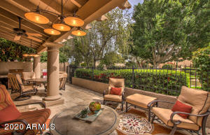 The well-designed covered patio includes a roomy conversation area. Across the way is the perfect spot to enjoy al fresco dining or games with friends. The open wrought iron fencing provides stunning daytime or evening views.