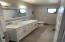 Remodeled guest bathroom with dual sink and shower/tub combo.
