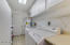 Plenty of storage in the laundry room along with a sink, counters, and cabinets.