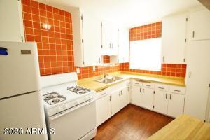 Kitchen with cool retro vibe! Original cabinets and fun/funky back splash!