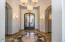 Enter the iron and glass doors into the beautiful foyer with custom tile details and gorgeous lighting