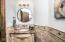 Thoughtfully located powder bath has beautiful stone wainscoting.