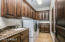 Laundry room with ample storage, a sink and built-in ironing board.