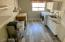 The laundry boasts natural light, sink, folding table with storage, second pantry and shelving.