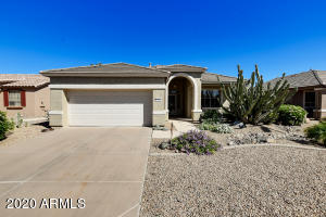 This lovely Orangewood model has a welcoming front porch and mature plants and trees. Don't let the square footage fool you... this home offers so much more than you would expect! The home is located in the guard-gated 55+ community of Arizona Traditions.