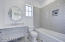 Private bath with Kohler soaking tub and custom tile accents.