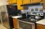 Nice stainless steel flat-top range/oven + stainless steel refrigerator.