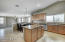 Large kitchen with island, eat in kitchen area, slab granite counters and lots of appliances