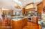 Massive chiseled edge granite slabs, warm cabinets and storage.