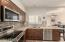 Stainless steel KitchenAid appliances, mosaic tile backsplash, and quartz countertops