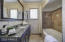 Remodeled bathroom features granite counters, custom wallpaper, Jacuzzi tub, Travertine shower walls with stone accent and Travertine flooring.