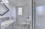 Master bath includes single vanity and walk-in tiled shower.