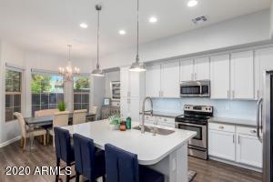 *Gorgeous designer kitchen w/ white shaker cabinetry, quartz countertops, glass tile back splash, pendant lighting + SS appliances*