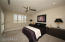 Guest bedroom w/plantation shutters & access to patio
