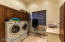 Large laundry room with built in cabinets and ironing board