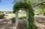 Decorative Garden Arbor Covered With Greenery Just Beyond Grass Area