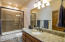 Full Guest Bath adorned with granite slab counters