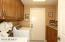 Laundry room features updated cabinets and granite countertop.
