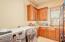 Spacious Laundry Room; Sink; GRANITE; Tall Raised Panel Cabinets; Travertine Tile Floors