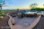 Banco seating around gas firepit, BBQ and swim up bar seating in this flagstone entertainment area