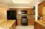 Kitchen features black appliances.