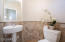 Tumbled travertine stone wainscoting with pedestal sink in powder room.