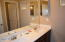 Guest bathroom with double sinks and door separating shower and toilet room