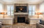 Family room features custom fireplace and cabinetry.