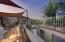 Custom outdoor kitchen featuring built in BBQ, lighting, sink, burner, frig & storage.
