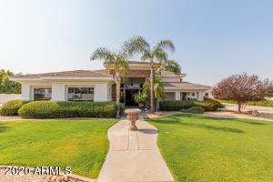Stunning move-in ready custom home with lush tropical mature landscaping.