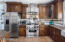 You'll Love Cooking In This Chef's Kitchen With Gas Range, Custom Cabinetry, Large Island & Farm Sink