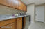 Laundry room and separate storage room with shelving system