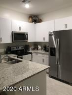 with granite counters, SS appliances, pendant lights, & breakfast bar!