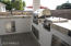 Outdoor kitchen with built in grill, sink and storage areas.