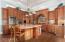Alder cabinets, Crown Crema granite, stone backsplash, wall ovens, and large island