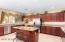 Kitchen with gas range & stainless steel appliances.