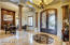 Grand Entry with Glass and Iron Front Door, Coffered Ceilings and Beautiful, Neutral Stone Flooring