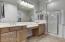 Downstairs master bath has double sink vanity.