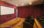 Walls embellished in velvet drapes and six electronic reclining theater seats