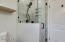 Walk-in tile shower, glass swing door, and Moen fixtures.