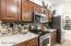 Large kitchen with island, granite counters and rock backsplash